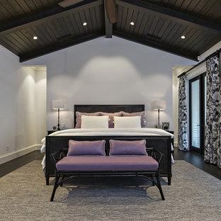 Modelo de habitación de invitados mediterránea, grande, con paredes blancas y suelo de madera oscura