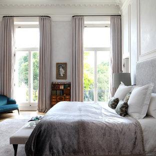 Classic bedroom in London with grey walls, medium hardwood flooring and brown floors.