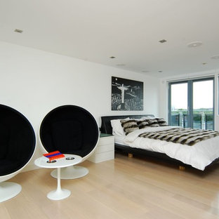 Contemporary bedroom in Berkshire with white walls and light hardwood flooring.