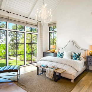 Beach style master medium tone wood floor bedroom photo in Dallas with white walls and no fireplace