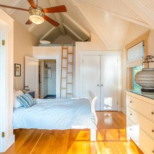 Diseño de dormitorio costero, sin chimenea, con paredes beige, suelo de madera en tonos medios y suelo amarillo