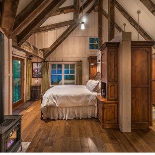 Diseño de dormitorio principal, de estilo de casa de campo, grande, con paredes beige, suelo de madera en tonos medios y estufa de leña
