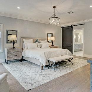 ヒューストンの中くらいのトランジショナルスタイルのおしゃれな主寝室 (グレーの壁、淡色無垢フローリング、茶色い床) のレイアウト