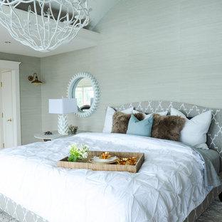 Ejemplo de dormitorio principal, costero, grande, con paredes grises, suelo de madera clara, chimenea tradicional, marco de chimenea de piedra y suelo marrón