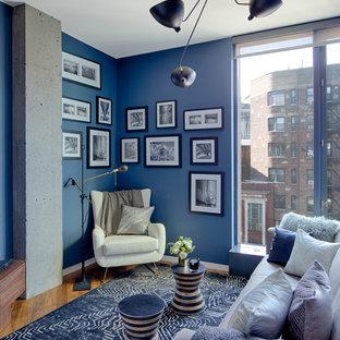 Modelo de dormitorio contemporáneo con paredes azules, suelo de madera en tonos medios y suelo marrón