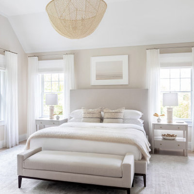 Example of a large classic master light wood floor and brown floor bedroom design in New York with beige walls and no fireplace