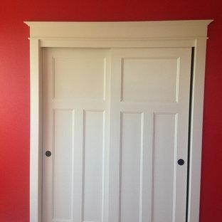 Diseño de dormitorio principal, de estilo americano, con paredes rojas y moqueta