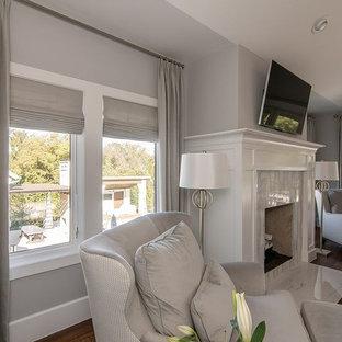 Geräumiges Klassisches Hauptschlafzimmer mit grauer Wandfarbe, dunklem Holzboden, Kamin, gefliester Kaminumrandung und braunem Boden in Dallas