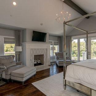 ダラスの巨大なトランジショナルスタイルのおしゃれな主寝室 (グレーの壁、濃色無垢フローリング、標準型暖炉、タイルの暖炉まわり、茶色い床) のインテリア