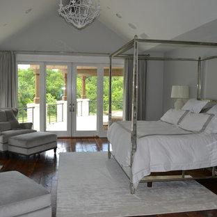 Diseño de dormitorio principal, clásico renovado, extra grande, con paredes grises, suelo de madera oscura, chimenea tradicional, marco de chimenea de baldosas y/o azulejos y suelo marrón