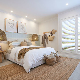 Inspiration for a beach style bedroom in Melbourne with white walls, light hardwood floors and beige floor.