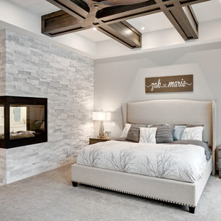 Large transitional master bedroom in Calgary with grey walls, carpet, a two-sided fireplace, a stone fireplace surround and grey floor.