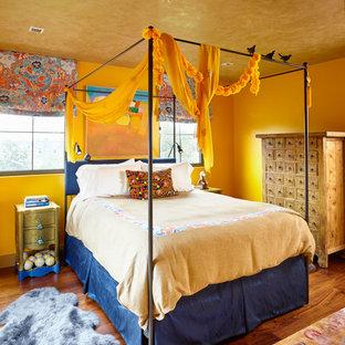 Aménagement d'une chambre éclectique avec un mur jaune et un sol en bois brun.