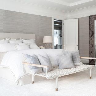 Réalisation d'une très grand chambre parentale tradition avec un mur beige, un sol en bois foncé, une cheminée standard et un manteau de cheminée en pierre.