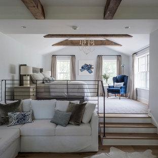 Modelo de dormitorio tipo loft, de estilo de casa de campo, grande, sin chimenea, con paredes grises y suelo de madera en tonos medios