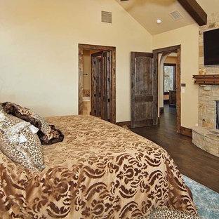 Diseño de dormitorio principal, rústico, grande, con paredes beige, suelo de madera en tonos medios, chimeneas suspendidas y marco de chimenea de piedra