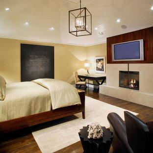 Foto de dormitorio principal, actual, grande, con paredes amarillas, suelo de madera oscura, chimenea tradicional y marco de chimenea de piedra