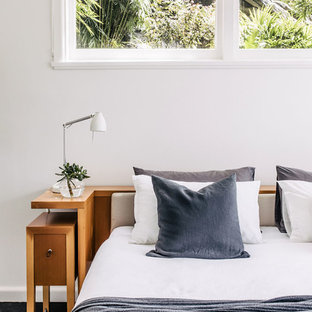 Photo of a contemporary bedroom in Sydney with white walls, painted wood floors and black floor.