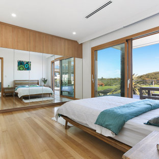 Inspiration for a contemporary bedroom in Sydney with white walls, medium hardwood floors and brown floor.