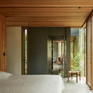 Modern master bedroom in Seattle with concrete floors, brown walls, grey floor, wood and wood walls.
