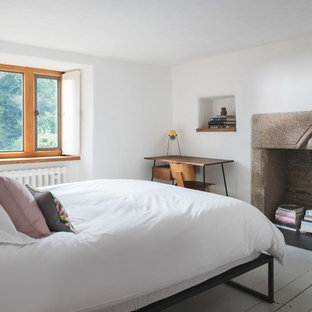 This is an example of a medium sized contemporary bedroom in Cornwall with white walls, painted wood flooring, a standard fireplace and white floors.