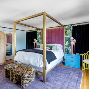 Mid-sized eclectic master bedroom in Los Angeles with multi-coloured walls, medium hardwood floors, no fireplace and wallpaper.