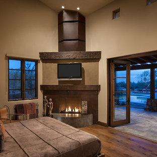 Ispirazione per una camera matrimoniale american style con pareti beige, parquet scuro e camino ad angolo