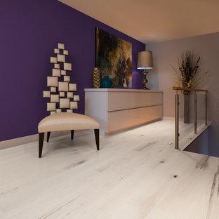 Modelo de dormitorio tipo loft, moderno, de tamaño medio, sin chimenea, con paredes púrpuras, suelo de madera clara y suelo beige