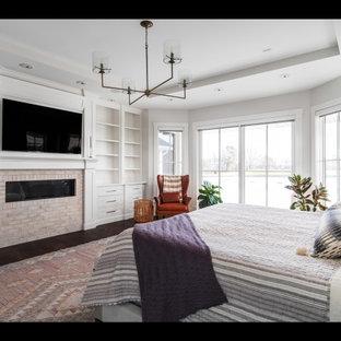 Diseño de dormitorio principal, campestre, grande, con paredes blancas, suelo de madera oscura, chimenea lineal y marco de chimenea de ladrillo