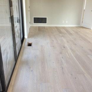 Diseño de dormitorio minimalista con suelo de madera clara y paredes grises