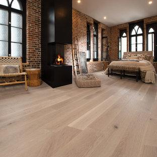 Modelo de dormitorio principal, industrial, grande, con paredes marrones, suelo de madera clara, chimenea lineal, marco de chimenea de metal y suelo beige