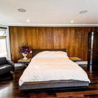 На фото: большая хозяйская спальня в стиле модернизм с коричневыми стенами, паркетным полом среднего тона, двусторонним камином и фасадом камина из плитки с