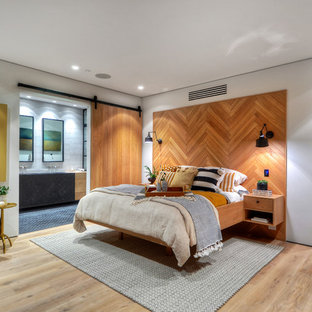 Example of a trendy master medium tone wood floor and brown floor bedroom design in Orange County with white walls
