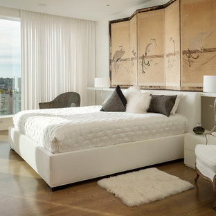 Photo of an asian master bedroom in Seattle with white walls and medium hardwood floors.