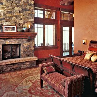 Foto de dormitorio principal, minimalista, extra grande, con paredes marrones, suelo de madera en tonos medios, chimenea tradicional y marco de chimenea de piedra