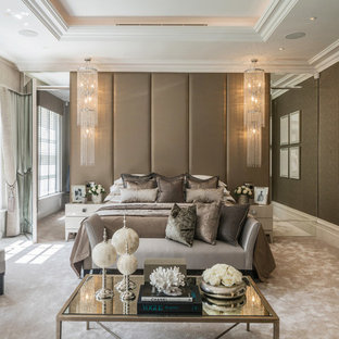 This is an example of a contemporary master bedroom in Berkshire with brown walls, carpet, a standard fireplace and beige floors.
