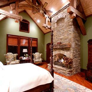 Modelo de dormitorio principal, rural, extra grande, con paredes verdes, suelo de madera en tonos medios, chimenea tradicional y marco de chimenea de piedra
