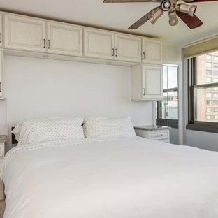 Foto di una camera matrimoniale di medie dimensioni con pareti bianche, pavimento in compensato, nessun camino e pavimento marrone