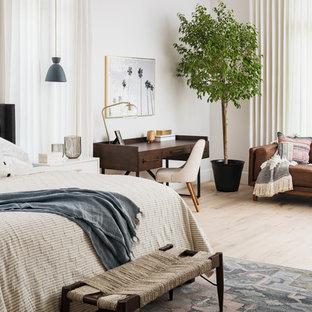 Diseño de dormitorio principal, tradicional renovado, grande, con paredes blancas, suelo de madera clara, chimenea tradicional, marco de chimenea de piedra y suelo beige