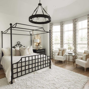 This is an example of a traditional master bedroom in Dallas with white walls, light hardwood flooring, no fireplace and beige floors.