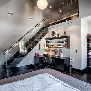 Expansive contemporary loft-style bedroom in New York with dark hardwood floors, no fireplace, grey walls and brown floor.
