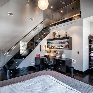 На фото: огромная спальня на антресоли в современном стиле с темным паркетным полом, серыми стенами и коричневым полом без камина