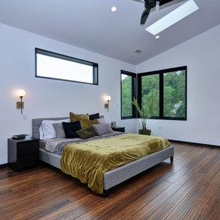 Ejemplo de dormitorio principal, industrial, grande, con paredes blancas, suelo de bambú y suelo marrón