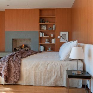 Imagen de dormitorio principal, contemporáneo, con suelo de madera clara, chimenea tradicional, marco de chimenea de hormigón y paredes marrones