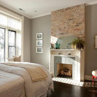 Modelo de dormitorio clásico renovado con paredes grises, suelo de madera oscura, chimenea tradicional y marco de chimenea de baldosas y/o azulejos
