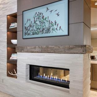 Idee per una camera matrimoniale moderna di medie dimensioni con pareti beige, moquette, camino bifacciale, cornice del camino in pietra e pavimento beige