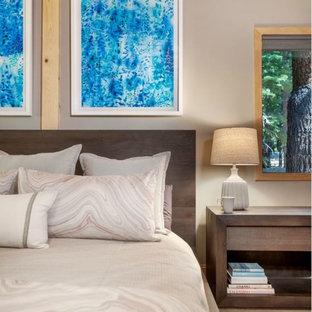 Modelo de dormitorio principal, moderno, de tamaño medio, con paredes beige, moqueta, chimenea de doble cara, marco de chimenea de piedra y suelo beige