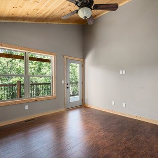 Example of a large mountain style master laminate floor and brown floor bedroom design in Other with gray walls