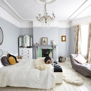 Cette image montre une grande chambre parentale victorienne avec un sol en bois peint, une cheminée standard et un sol blanc.