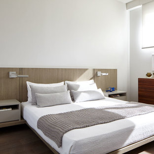 Inspiration for a mid-sized modern master bedroom in New York with white walls, medium hardwood floors and brown floor.